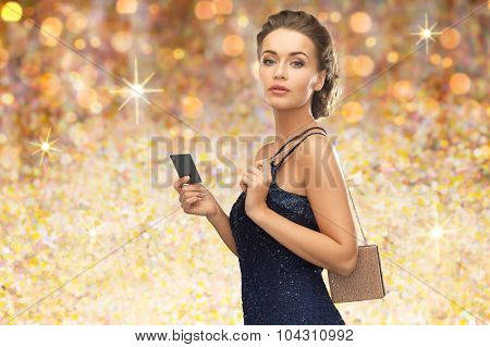 people, luxury, holidays and finance concept - beautiful woman in evening dress with vip card and handbag over golden lights background