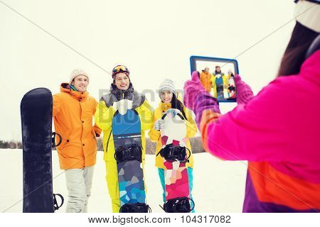 winter sport, technology, leisure, friendship and people concept - happy friends with snowboards and tablet pc computer taking picture outdoors