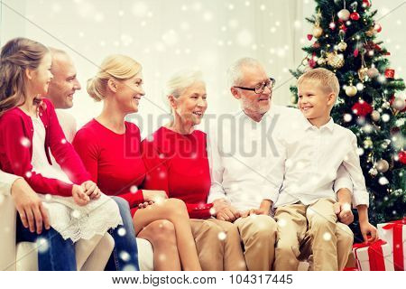 family, holidays, generation, christmas and people concept - smiling family sitting on couch at home