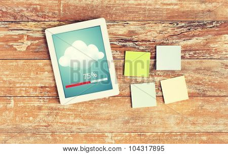 business, education, cloud computing and technology concept - close up of stickers and tablet pc computer transferring data on table