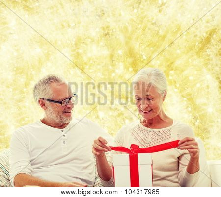 family, holidays, christmas, age and people concept - happy senior couple with gift box over yellow lights background