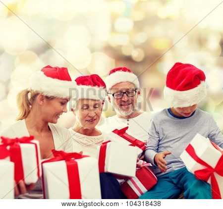 family, christmas, generation, holidays and people concept - happy family in santa helper hats with gift boxes sitting over lights background