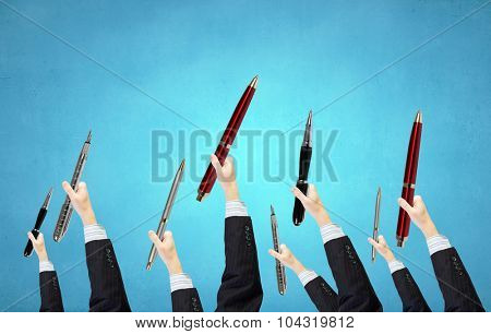 Many hands of business people holding automatic pen