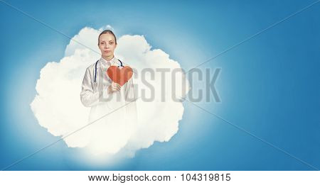 Young female doctor holding red heart in hands