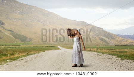 Woman with suitcase in white long dress and hat on countryside road