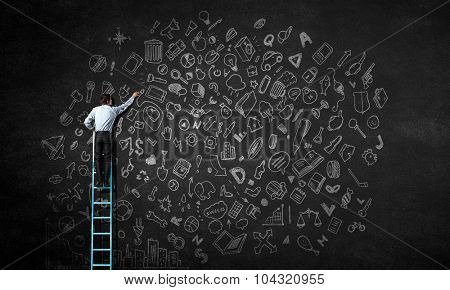 Rear view of businessman standing on ladder and writing business concepts on wall