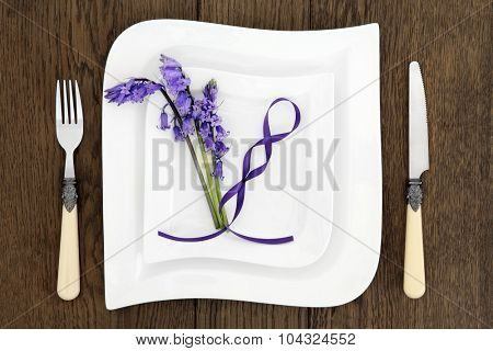 Table place setting with white porcelain dishes, antique cutlery, bluebells flowers and blue ribbon over old oak background.