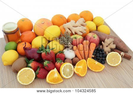 Large health food selection for cold and flu remedy with foods high in antioxidants and vitamin c on bamboo over white background.
