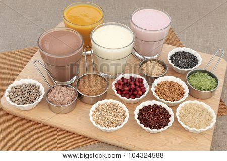 Body building health food with protein and fruit juice shakes, chocolate whey, wheatgrass, pomegranate and maca powder, seeds and oatmeal on a beech wood board.