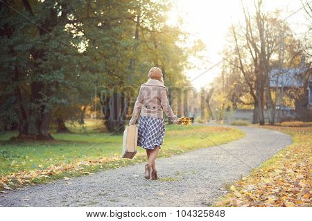 Attractive young woman walking with a bouquet of autumn leaves and a suitcase.
