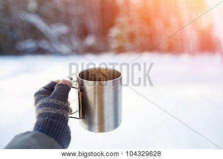 Gloved mitten hand holding a travel mug.