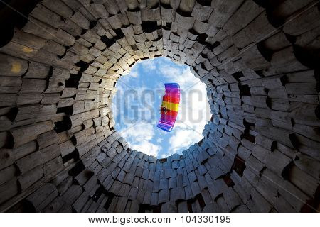 Paraplane in a blue sky. Bottom view through wood tower