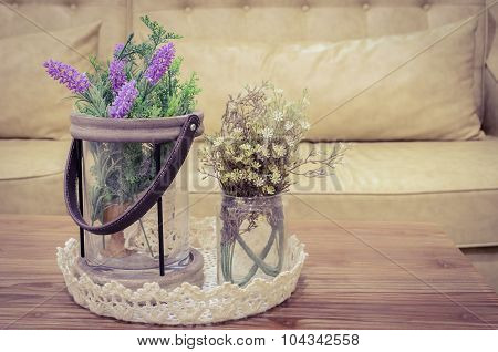 Artificial Flowers On Wooden Table With Sofa Background