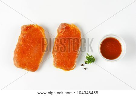 slices of raw pork tenderloin marinated in honey marinade on white background
