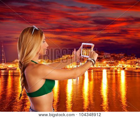 Blond tourist girl taking photos of Ibiza skyline at sunset photomount