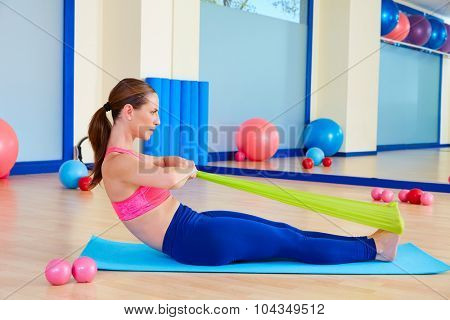 Pilates woman rowing rubber band exercise workout at gym indoor
