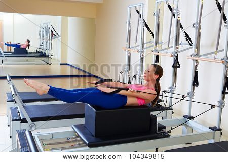 Pilates reformer woman back stroke exercise workout at gym indoor
