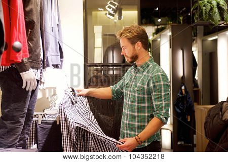 Male Shopper Looking At Clothes In Store