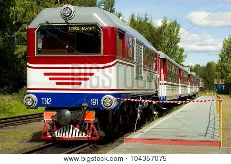 Red-white locomotive with trailer cars passenger stands on a platform in the forest