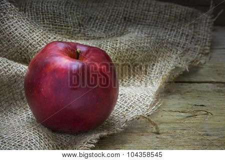 Single Red Christmas Apple On Rough Bag Fabric And Rustic Wood