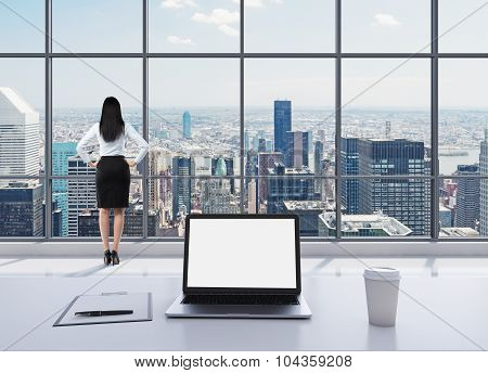 A Dressed Brunette Woman In Formal Clothes Is Standing In Modern Panoramic Office And Looking At New
