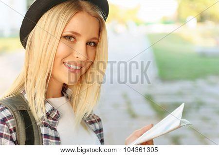 Cheerful girl holding map