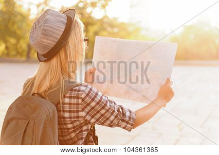Cheerful girl holding map