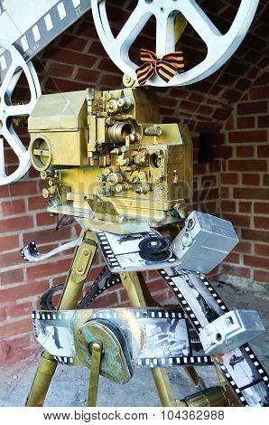 Old Film Movie Camera In The Span Of Novgorod Kremlin Fortress.