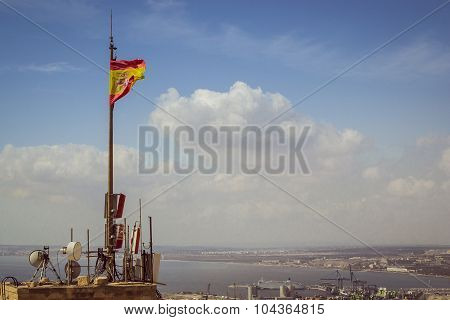 flag of Spain on a tower of the fortress of Santa Barbara in Alicante