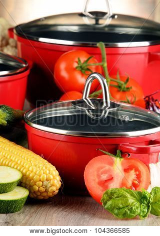 Composition With Red Steel Pots And Variety Of Fresh Vegetables