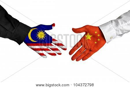Malaysia and China leaders shaking hands on a deal agreement