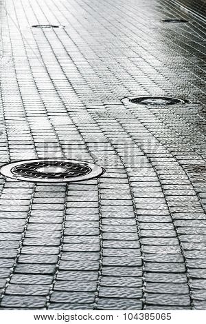 Sewer Manhole On Wet Cobblestone Street