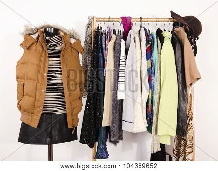 Wardrobe With Clothes Arranged On Hangers And A Winter Outfit On A Mannequin.
