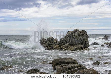 Waves breaking on the rocks .