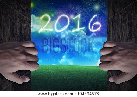 Hand Open Wooden Door To The City That Celebrate New Year 2016