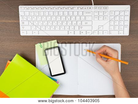 Humans hand writing in copy book with smartphone