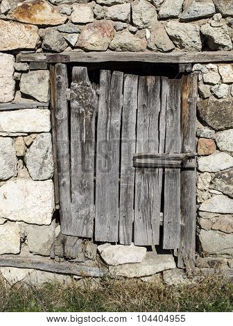 Old Stone Wall With Wooden Padlocked Door