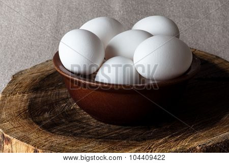 Eggs in a bowl on cutting board from side