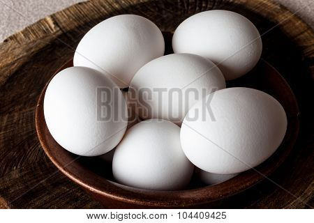 Eggs in a bowl on cutting board closeup from above