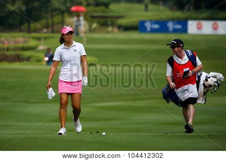 KUALA LUMPUR, MALAYSIA - OCTOBER 09, 2015: USA's Danielle Kang discusses with her caddy on the sixth hole fairway of the KL Golf & Country Club at the 2015 Sime Darby LPGA Malaysia golf tournament.