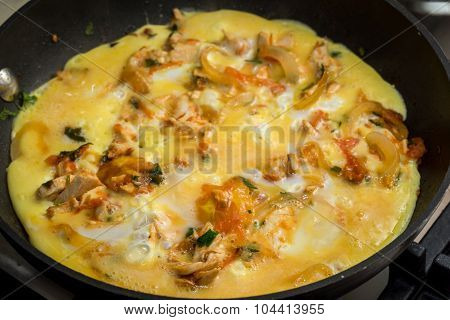 Close Up Of Cooking Omelette With Onion, Tomatoes, Chicken And Parsley On A Frying Pan