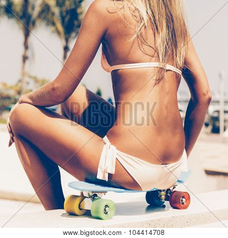 Sexy Suntanned Lady Sitting On The Blue Penny Board In The Park