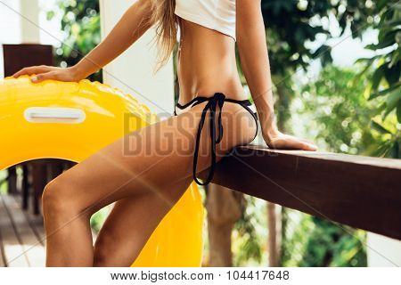 Pretty Athletic Girl In A Sexual Striped Bikini Is Sitting On The Railing Of The Terrace