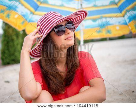 Girl Sitting Under Umbrella On The Sand