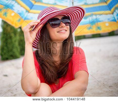 Smiling Girl Sitting Under Umbrella On The Sand