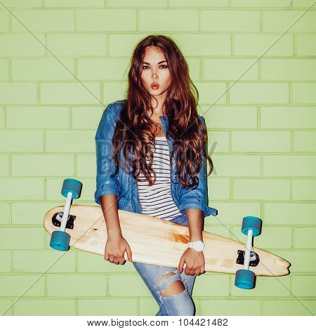 Beautiful Long-haired Girl With A Wooden Long Skateboard Near A Green Brick Wall