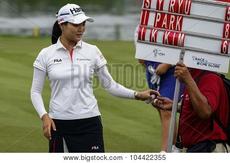 KUALA LUMPUR, MALAYSIA - OCTOBER 09, 2015: South Korea's So Yeon Ryu passes an autographed golf ball to a volunteer after finishing her day's play at the 2015 Sime Darby LPGA Malaysia golf tournament.