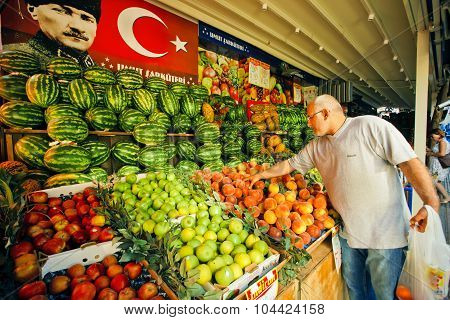 Man chooses peaches on a market stand in Istanbul