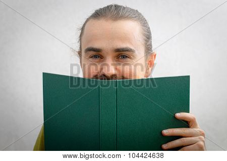 Man Smiling From Behind The Book