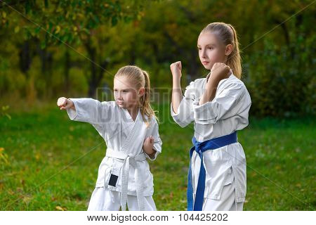 girls in white kimono during training karate exercises at summer outdoors
